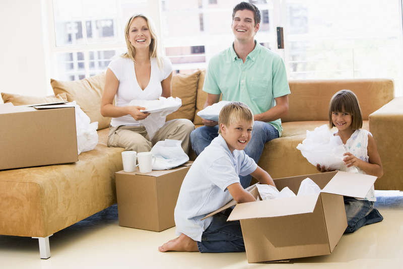 Family UnpaOpen New Premises With Our Hermosa Beach Movers1cking Boxes In New Home Smiling